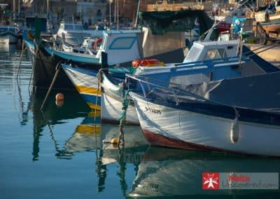 A traditional luzzu with its more modern counterpart fishing boats.