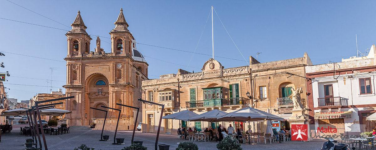The main square of Marsaxlokk and its parish church.